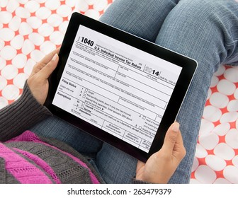 Woman  filing federal income tax over internet using form 1040 on mobile tablet computer and wireless technology