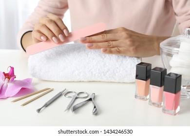 Woman filing nails covered with polish at table, closeup