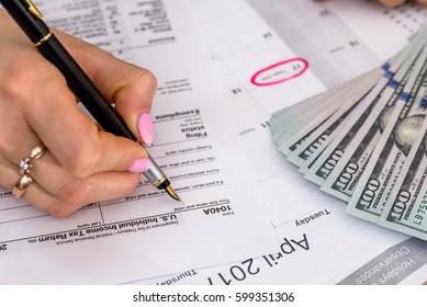 Woman filing US tax form. annual budget.