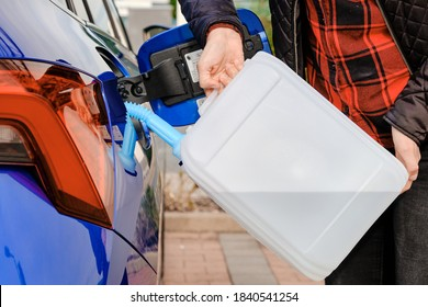 Woman filling a diesel engine fluid from canister into the tank of blue car. Diesel exhaust fluid for reduction of air pollution.