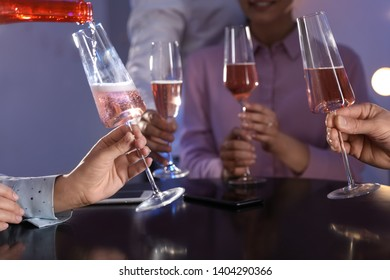 Woman filling glass with champagne and her friends at table in bar, closeup