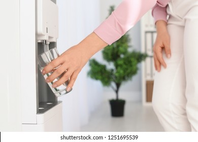 Woman filling glass from water cooler at workplace, closeup