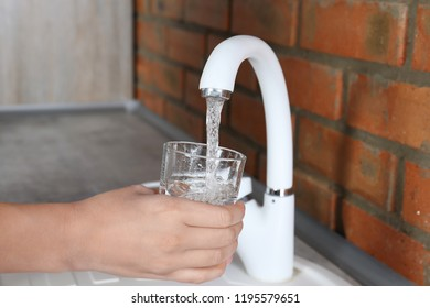 Woman filling glass with water from faucet in kitchen, closeup