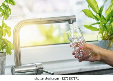 Woman filling glass with water from faucet in kitchen - Shutterstock ID 1275157171