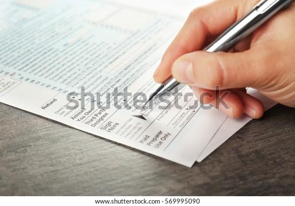 Woman filling individual income tax return form, closeup