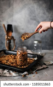 Woman filling a mason jar with homemade granola. Healthy vegan snack easily prepared at home. Visible body parts, hands of an elderly woman.