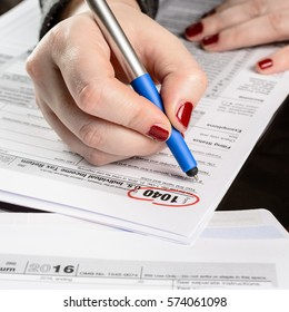Woman fills the tax form, working with tax documents.Form 1040 Individual Income Tax return form. United States Tax forms 2016/2017.