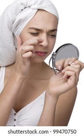 Woman finding an acne on her nose wit towel on her head