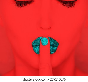 woman with finger on lips .