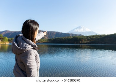 Woman finger pointing to Mount Fuji at Lake yamanaka