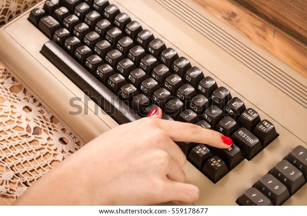 Woman finger press button on old computer keyboard