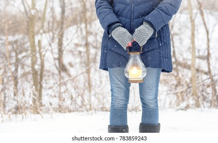 woman in fingerless gloves standing outside holding lantern while snow is falling
