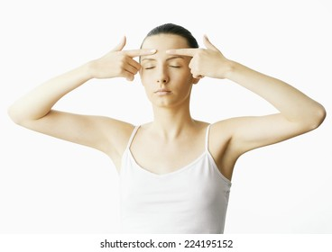 Woman with fingers on forehead and eyes closed