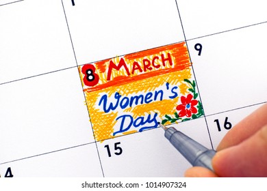 Woman fingers with pen writing reminder Women's day in calendar. Close-up.