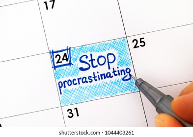 Woman fingers with pen writing reminder Stop Procrastinating in calendar. Close-up.