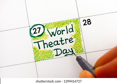 Woman fingers with pen writing reminder World Theatre Day in calendar. 27 March. Close-up.