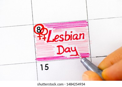Woman fingers with pen writing reminder Lesbian Day in calendar. Close-up.