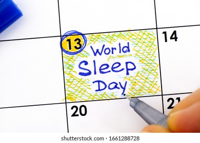Woman fingers with pen writing reminder World Sleep Day in calendar. March 13.