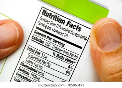 Woman fingers with protein jar. Reading nutrition facts.  Close-up.