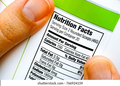Woman fingers with protein jar. Reading nutrition facts. Closeup.