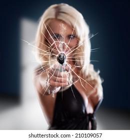 woman firing a gun through a window