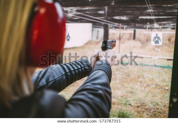 Woman firing with pistol on target at the shooting range. Close-up.