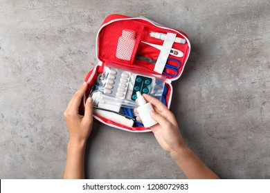 Woman with first aid kit on gray background, top view