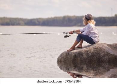 woman fisher sitting on summer sea beach