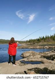 Woman fishing by a lake