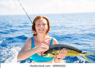 Woman fishing Dorado Mahi-mahi fish happy with trolling catch on boat deck