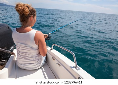 Woman fishing with trolling catch on motorboat deck, rear view