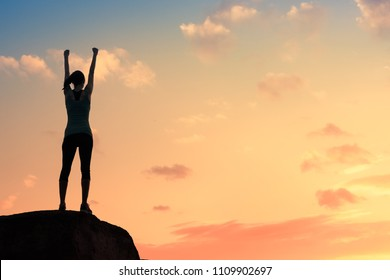 Woman with fist in the air standing high up on a mountain top. Feeling motivated.