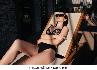 Woman with fit body in fashionable elegant pink bikini swimsuit and sunglasses lying down and posing with fishnet shadow pattern on her body beside the swimming pool - black, white and pink photo