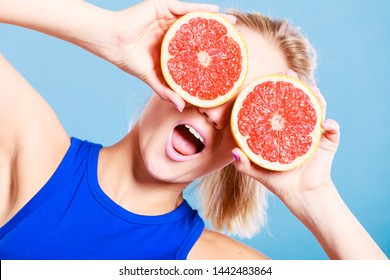 Woman fit girl holding two halfs of grapefruit citrus fruit in hands, covering her eyes. Healthy diet food. Happiness holidays fun concept.
