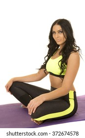 A woman in fitness clothing sitting on a yoga mat.