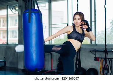 A woman in a fitness suit is kicking a sandbag in the gym.