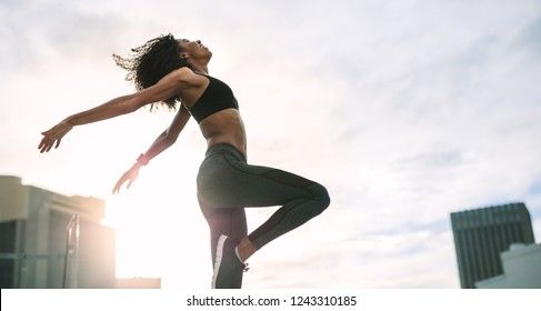 Woman in fitness wear jumping high standing on rooftop with sun flare in the background. Female athlete doing exercises in the morning on terrace of a building.