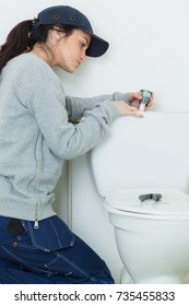 Woman fitting toilet cistern