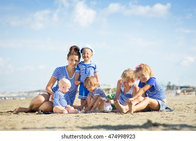 Woman with five children on the beach
