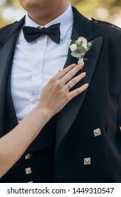 woman fixes accessories on the groom Scottish tuxedo