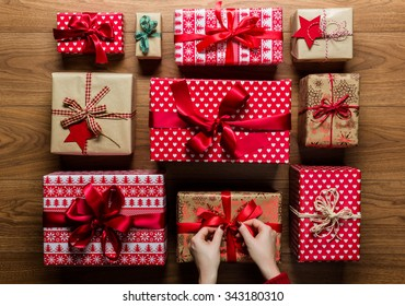 Woman fixing a bow on beautifuly wrapped vintage christmas presents on wooden background, view from above