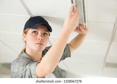woman fixing ceiling fixture