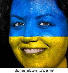 Woman with flag painted on her face to show Ukraine support in sports