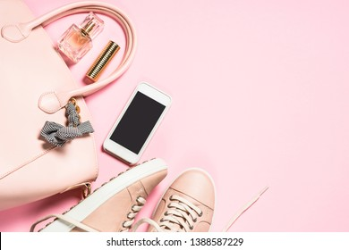 Woman flat lay background. Fashion accessories and cloth - shoes, handbag, smartphone and perfume on pink background. Top view copy space.