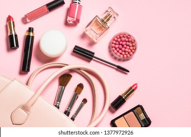 Woman flat lay makup background with cosmetics.  Cream, lipstick, powder, mascara and brushes. Top view on pink background, copy space.