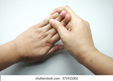 Woman flexing/stretching fingers against hand on gray background.