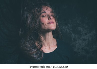 Woman flinging hair up and towards her face