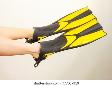 Woman with flippers having fun presenting snorkeling fins on her feet studio shot on grey. Funny girl dreaming about swimming summer vacation