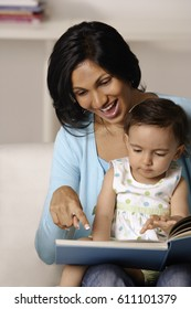 woman flipping picture book with baby