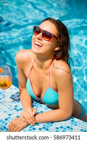 Woman floating  in the  blue pool. Summer holiday idyllic.